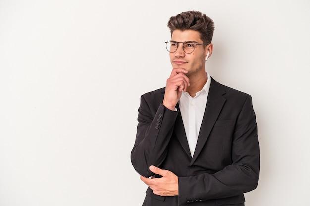 Jonge blanke zakenman met een koptelefoon op een witte achtergrond die zijwaarts kijkt met een twijfelachtige en sceptische uitdrukking.