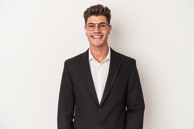 Jonge blanke zakenman met koptelefoon geïsoleerd op een witte achtergrond gelukkig, glimlachend en vrolijk.