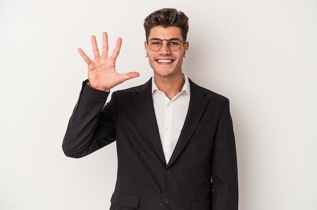 Jonge blanke zakenman met koptelefoon geïsoleerd op een witte achtergrond glimlachend vrolijk nummer vijf met vingers.