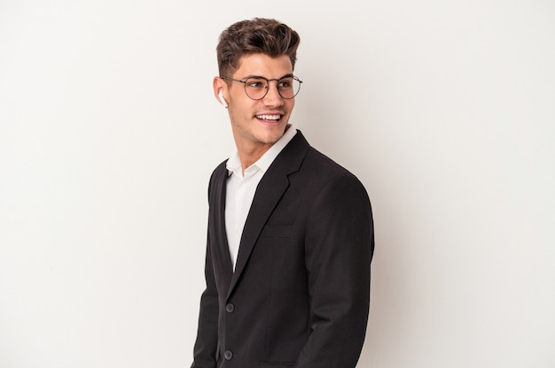 Jonge blanke zakenman met koptelefoon geïsoleerd op een witte achtergrond kijkt opzij glimlachend, vrolijk en aangenaam.