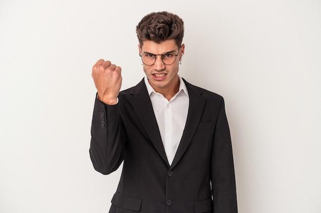 Jonge blanke zakenman met koptelefoon geïsoleerd op een witte achtergrond met vuist naar camera, agressieve gezichtsuitdrukking.