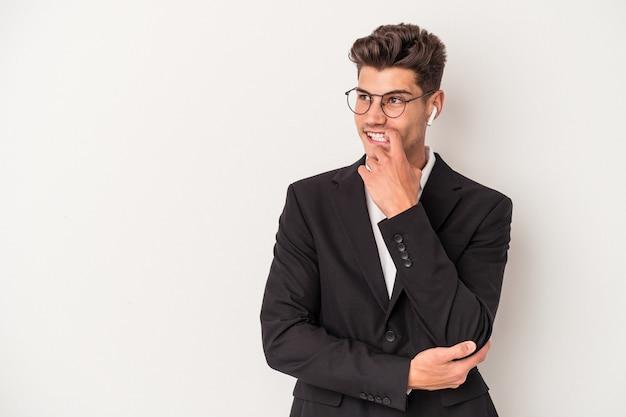 Jonge blanke zakenman met koptelefoon geïsoleerd op een witte achtergrond ontspannen denken over iets kijken naar een kopie ruimte.