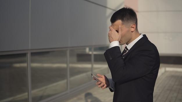 Jonge blanke zakenman met smartphone staat boos met de hand op zijn hoofd tegen de achtergrond van het bouwen van grote bedrijven
