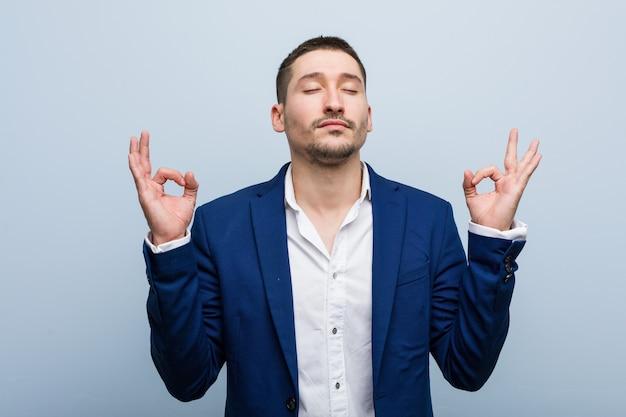 Jonge blanke zakenman ontspant na een zware werkdag, hij voert yoga uit.