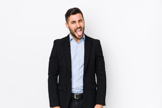 Jonge blanke zakenman tegen een witte muur grappig en vriendelijk tong uitsteekt.