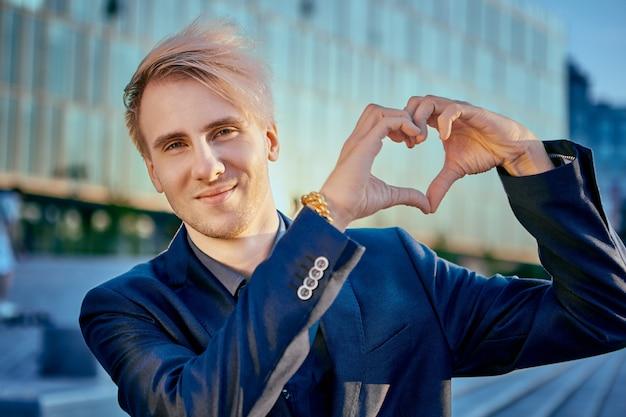 Jonge blanke zakenman toont hart met zijn handen