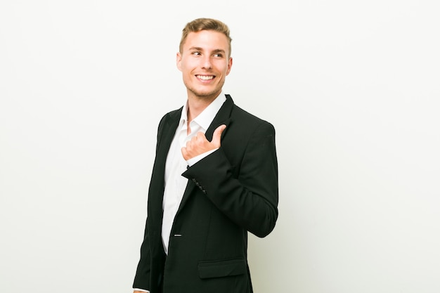 Jonge blanke zakenman wijst met duim vinger weg, lachen en zorgeloos.