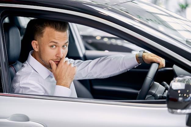 Jonge blanke zakenman zit binnenkant auto achter het stuur