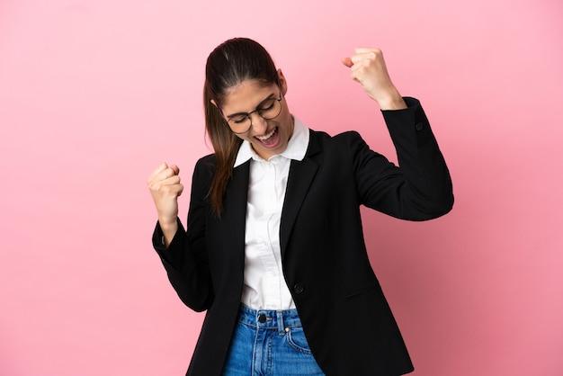 Jonge blanke zakenvrouw geïsoleerd op roze achtergrond die een overwinning viert