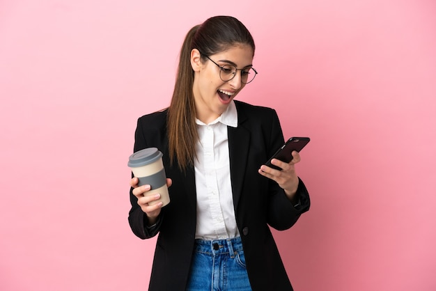 Jonge blanke zakenvrouw geïsoleerd op roze achtergrond met koffie om mee te nemen en een mobiel