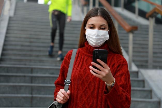Jonge blanke zakenvrouw in medisch masker gaat de trap af