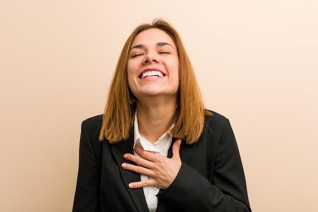 Jonge blanke zakenvrouw lacht hardop hand houden op de borst.