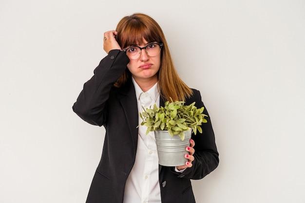 Jonge blanke zakenvrouw met een plant geïsoleerd op een witte achtergrond geschokt, ze heeft een belangrijke vergadering onthouden.