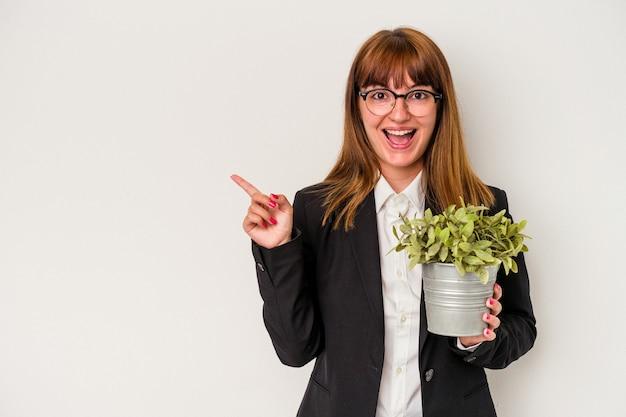 Jonge blanke zakenvrouw met een plant geïsoleerd op een witte achtergrond glimlachend en opzij wijzend, iets tonend op lege ruimte.