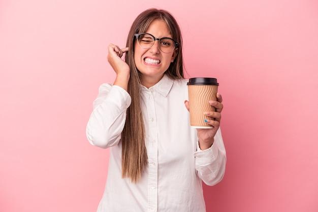 Jonge blanke zakenvrouw met een take-away geïsoleerd op een roze achtergrond die oren bedekt met handen.