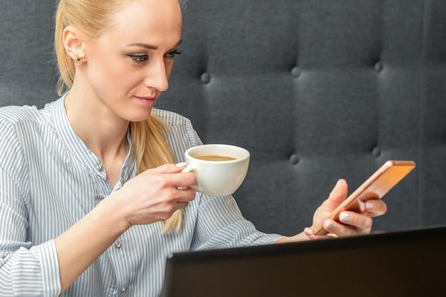 Jonge blanke zakenvrouw met smartphone en kopje koffie thuis werken op kantoor