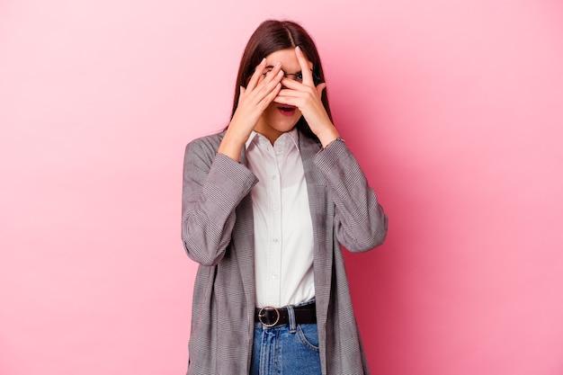 Jonge blanke zakenvrouw op roze knipperen door angstige en nerveuze vingers.