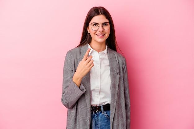 Jonge blanke zakenvrouw op roze wijzend met vinger naar je alsof uitnodigend dichterbij komen.