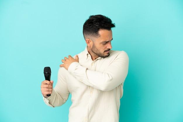 Jonge blanke zanger man geïsoleerd op blauwe achtergrond die lijdt aan pijn in de schouder omdat hij moeite heeft gedaan