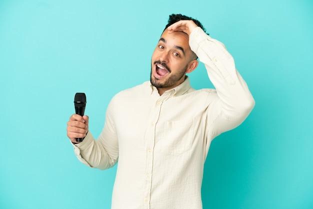 Jonge blanke zanger man geïsoleerd op blauwe achtergrond doet verrassingsgebaar terwijl hij naar de zijkant kijkt