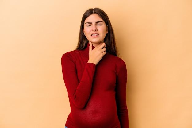 Jonge blanke zwangere vrouw geïsoleerd op beige achtergrond lijdt aan pijn in de keel als gevolg van een virus of infectie.
