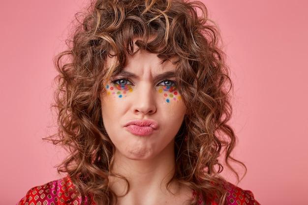 Jonge blauwogige vrouw met bruin krullend haar en feestelijke make-up die provocerend kijkt en haar wenkbrauwen fronst, geïsoleerd