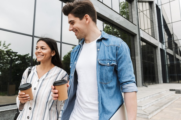 Jonge blij opgewonden geweldige verliefde paar studenten buiten op straat wandelen koffie drinken met elkaar praten.