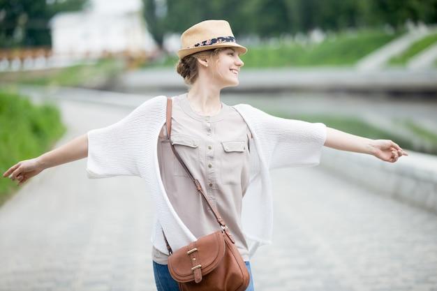 Jonge blije gelukkige reiziger vrouw in strohoed genieten van haar reis