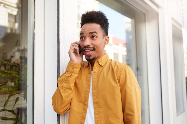Jonge blije verbaasde donkere man in een geel overhemd loopt over straat, spreekt aan de telefoon, hoort ongelooflijk nieuws, met wijd open mond en ogen, kijkt verbaasd.