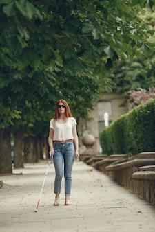 Jonge blinde met lange stok wandelen in een stad