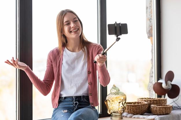 Jonge blogger die zichzelf naast venster opneemt