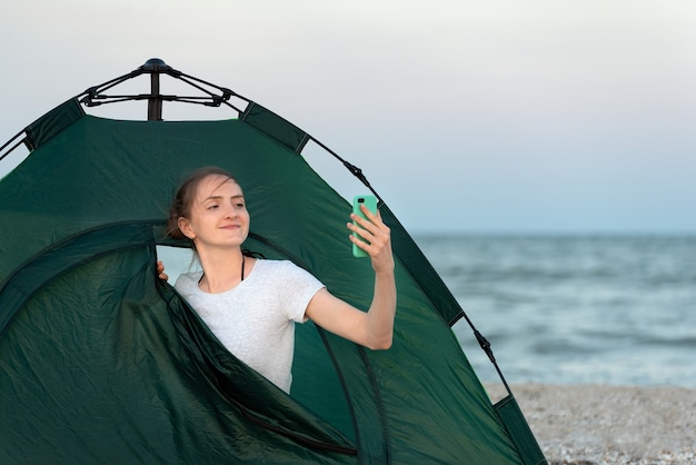 Jonge blogger in tent op zandstrand