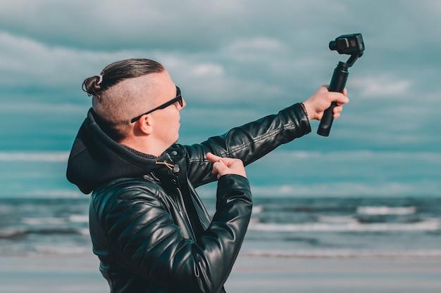 Jonge blogger in zonnebril selfie maken of video streamen op het strand met behulp van actiecamera met gimbal camera stabilizer.