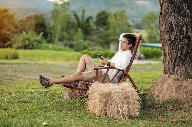 Jonge blogger man met smartphone tijdens het ontspannen in de tuin