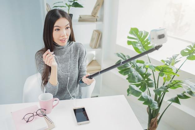 Jonge blogger neemt een video op waarin ze op de telefoon naar muziek luistert