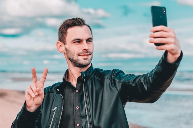 Jonge blogger selfie maken of video streamen op het strand met behulp van zwarte smartphone.