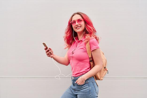 Jonge blogger-vrouw met roze geverfde haren die in de buurt van de grijze muur blijven en smartphone gebruiken