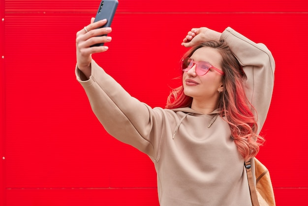 Jonge blogger vrouw met roze geverfde haren verblijft in de buurt van de rode muur en selfie maken door smartphone