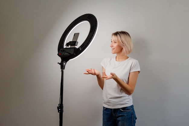 Jonge bloggermeisje zendt thuis live online uit met een ringlamp en een smartphone