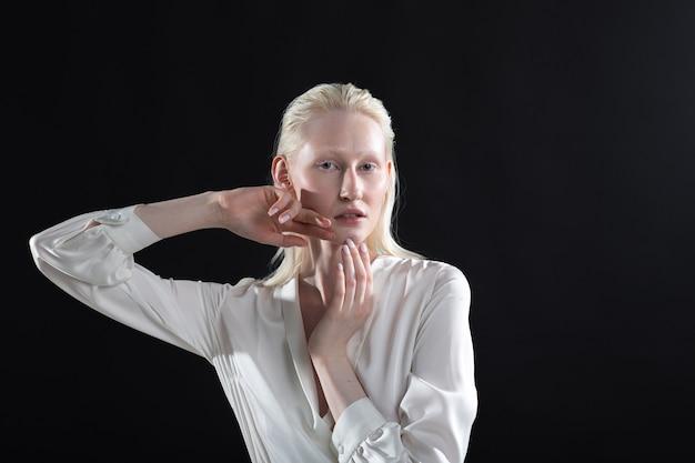 Jonge blonde albino-vrouw die gezichtsgymnastiek zelfmassage en verjongende oefeningen op zwarte achtergrond bouwt.