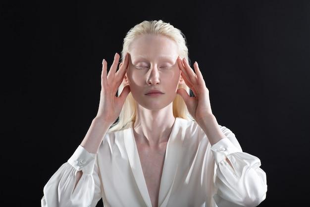 Jonge blonde albino-vrouw die gezichtsgymnastiek zelfmassage en verjongende oefeningen op zwarte achtergrond doet