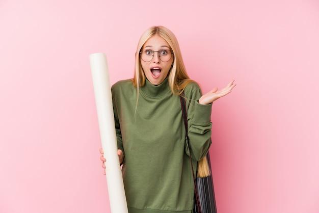 Jonge blonde architectuurstudent die een overwinning of een succes viert