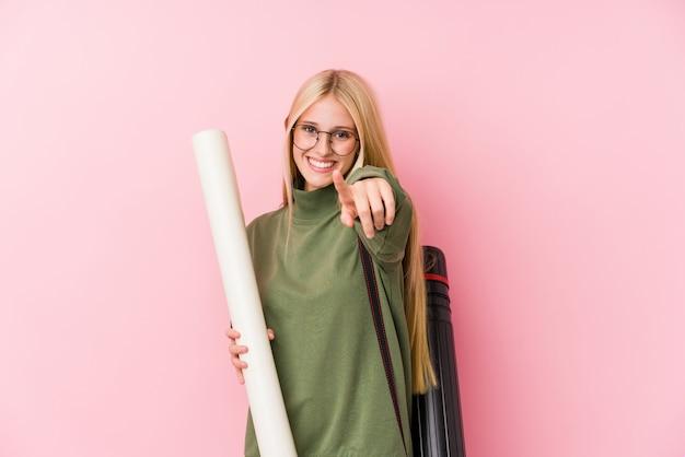Jonge blonde architectuurstudent vrolijke glimlachen die aan voorzijde richten.