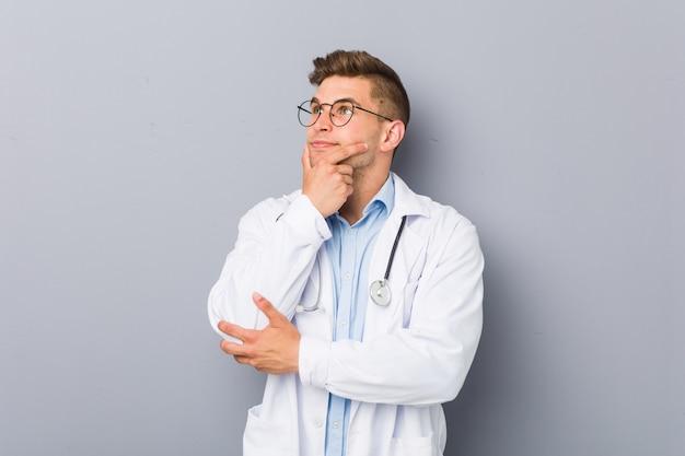 Jonge blonde artsenmens zijdelings met twijfelachtige en sceptische uitdrukking.