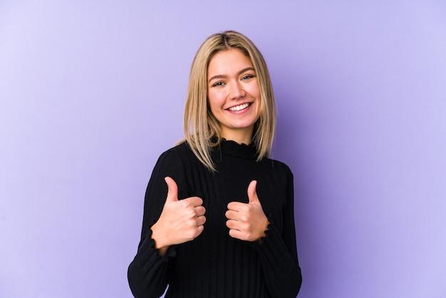 Jonge blonde blanke vrouw die beide duimen opheft, glimlachend en zelfverzekerd.