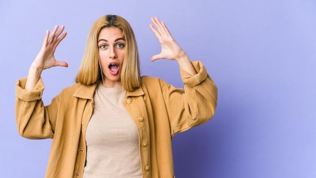Jonge blonde blanke vrouw die een overwinning of succes viert, hij is verrast en geschokt.
