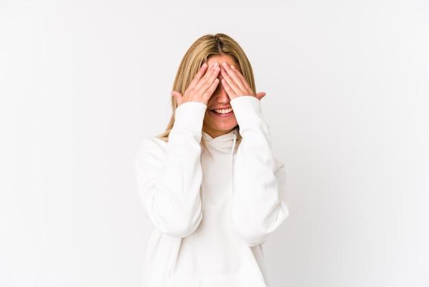 Jonge blonde blanke vrouw geïsoleerd bedekt ogen met handen, glimlacht in het algemeen wachtend op een verrassing.