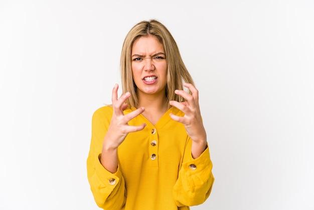 Jonge blonde blanke vrouw geïsoleerd boos schreeuwen met gespannen handen.