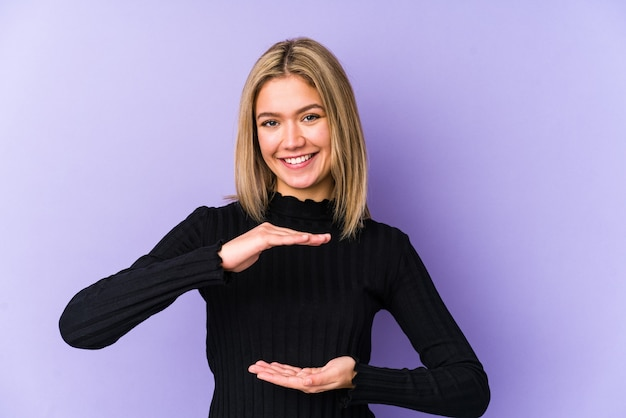 Jonge blonde blanke vrouw geïsoleerd iets met beide handen te houden, productpresentatie.