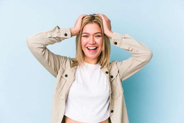 Jonge blonde blanke vrouw geïsoleerd lacht vreugdevol handen op het hoofd te houden. geluk concept.